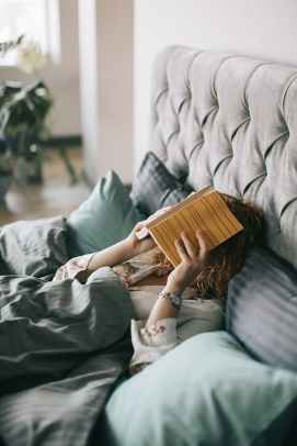 woman covering face with book on bed